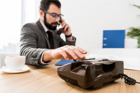 businessman dialing number with stationary telephone in office Фото со стока