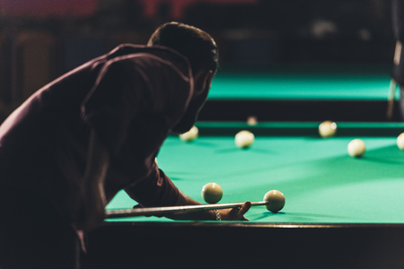 back view of man playing in russian pool at bar