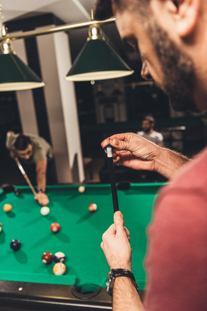 cropped image of man chalking billiard cue at bar with friends