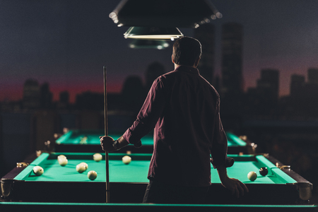 back view of successful man standing beside pool table with at bar Archivio Fotografico