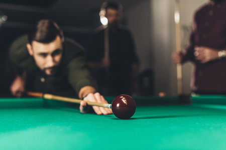 young successful handsome man playing in russian pool at bar with friends