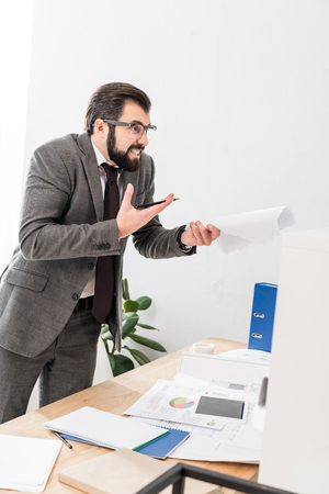 irritated businessman holding documents and screaming at someone Stock Photo