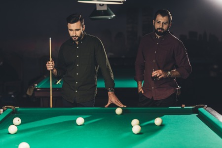 couple of successful men standing beside pool table with drink at bar