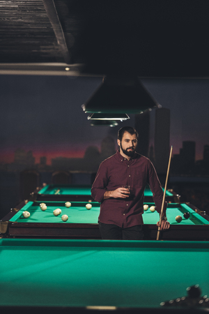 successful handsome man standing beside pool table with drink at bar