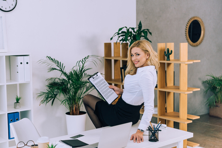 seductive woman sitting on table with documents and looking at camera Standard-Bild