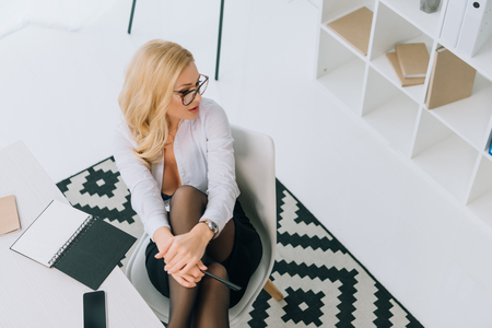 overhead view of sexy woman sitting in chair and looking away Standard-Bild