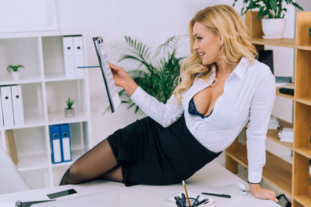 sexy woman sitting on table and reading documents Standard-Bild