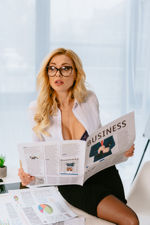 attractive sexy businesswoman sitting on table and holding business newspaper
