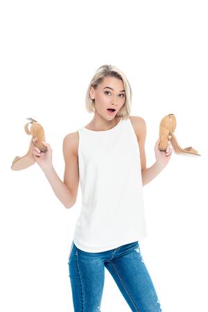 surprised woman holding stylish heels, isolated on white 版權商用圖片