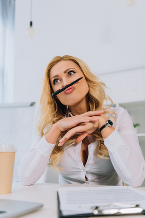 businesswoman grimacing and making mustache with pen