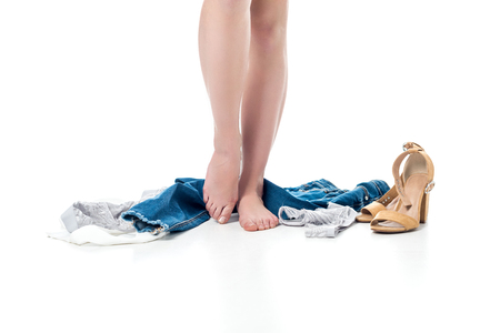 cropped view of female legs standing with clothes around, isolated on white