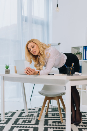 attractive sexy businesswoman leaning on table and taking selfie with smartphone