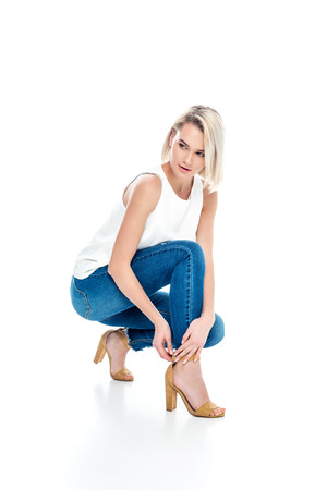 attractive woman posing in jeans and heels, isolated on white
