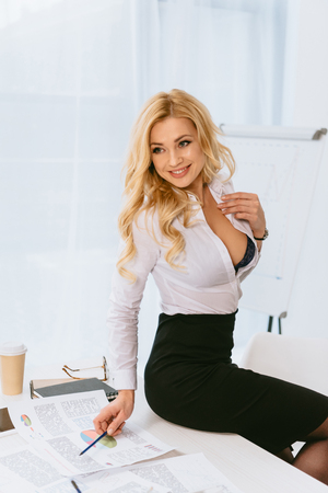 sexy woman with unbuttoned shirt sitting on table with pencil Banque d'images