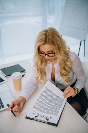 overhead view of sexy businesswoman reading working contract