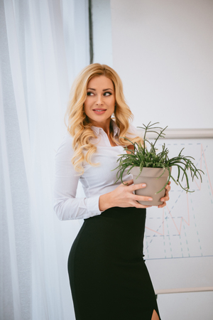businesswoman holding flowerpot with green plant and looking away