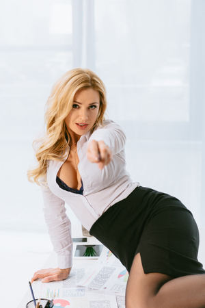 sexy woman sitting on table and pointing on camera