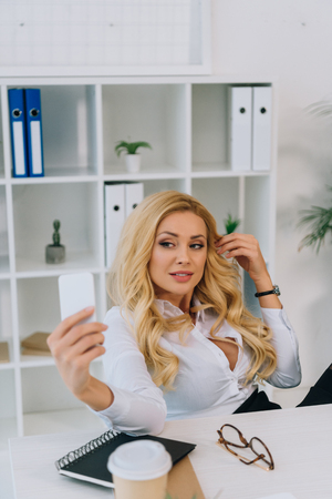 sexy blonde businesswoman taking selfie at working place with smartphone Stock Photo - 104562209