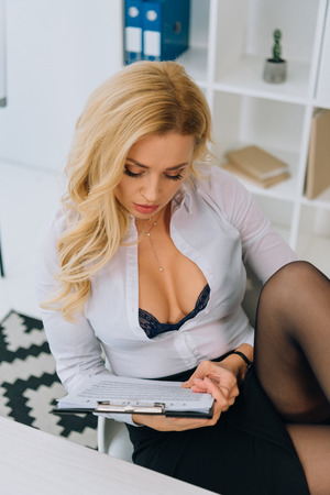 sexy woman with decollete reading working contract Standard-Bild