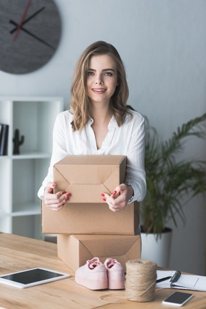portrait of smiling self-employed businesswoman with parcels looking at camera at home office