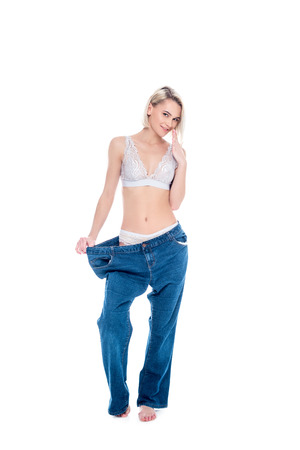 slim girl in old jeans old jeans after losing weight, isolated on white Stock fotó