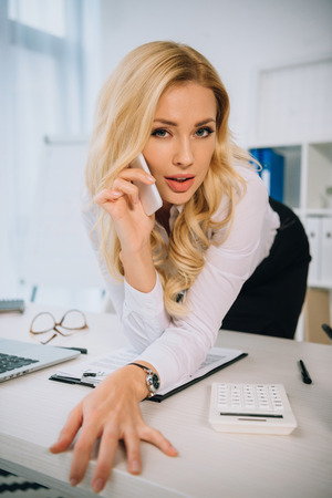 sexy businesswoman leaning on table and talking by smartphone