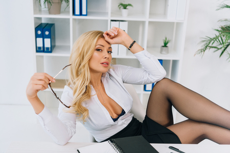 tired sexy woman sitting in chair, holding glasses and looking at camera Zdjęcie Seryjne - 104562422