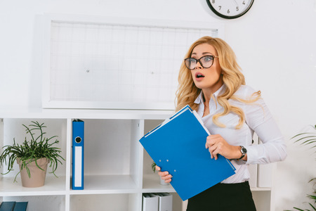 shocked woman standing with folder in office Stock Photo