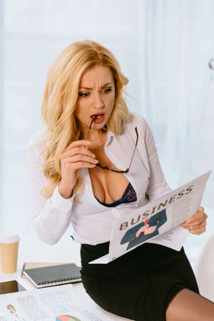 attractive surprised woman biting glasses while reading business newspaper 版權商用圖片