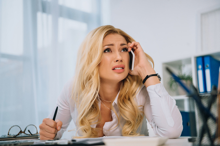 exhausted businesswoman talking by smartphone in office Stock Photo