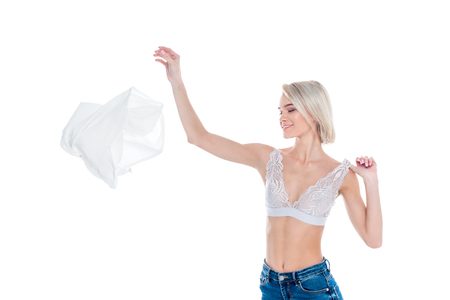 attractive sexy girl in bra throwing away clothes, isolated on white Reklamní fotografie