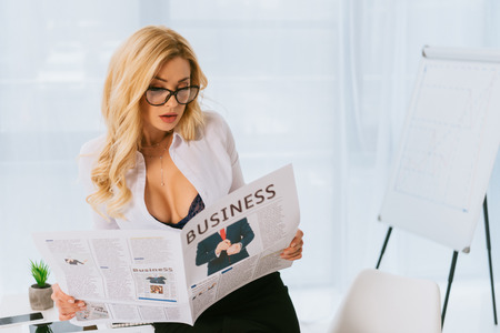 attractive sexy woman standing and reading business newspaper