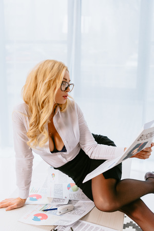 sexy attractive woman reading business newspaper