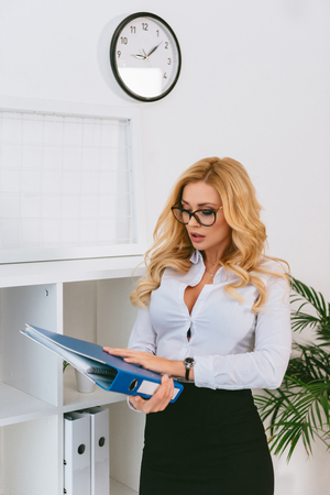 sexy woman holding folder with documents