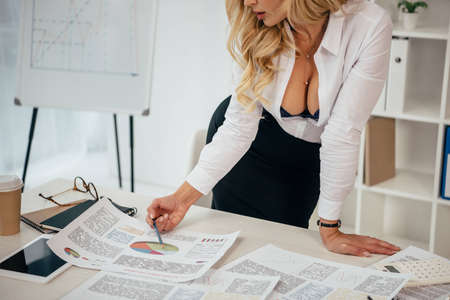 cropped image of sexy woman looking at documents