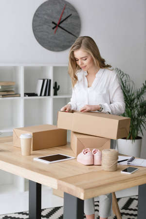 portrait of beautiful entrepreneur packing products in cardboard boxes at home office