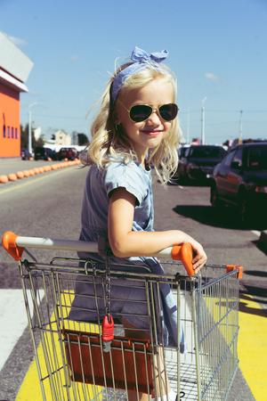 little child having fun in shopping cart at parking Stok Fotoğraf