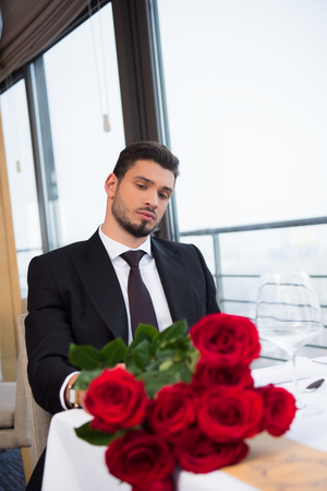 portrait of young man in suit with bouquet of red roses waiting for girlfriend in restaurant 写真素材
