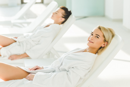 attractive young women lying on sunbeds at spa center Stock Photo