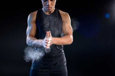 young african american sportsman clapping hands with talc on black Stock Photo