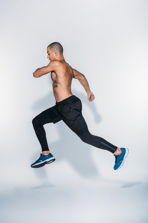 side view of african american sportsman jumping on white Stockfoto