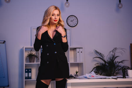 seductive businesswoman standing in jacket and stockings