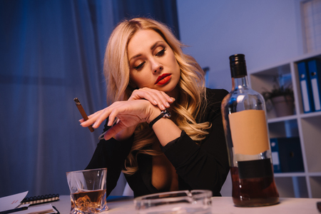 seductive woman sitting with cigar and looking at bottle of whiskey in office