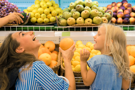 mother and daughter choosing fruits in supermarket