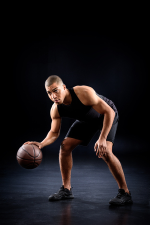 african american basketball player bouncing ball on black