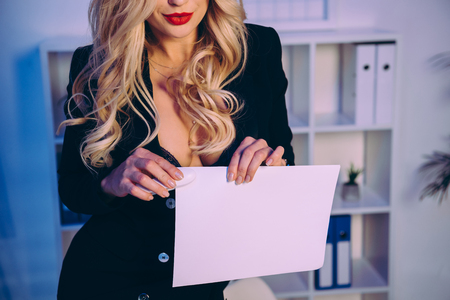 cropped image of sexy woman stapling papers with stapler 写真素材