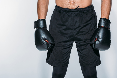Cropped image of boxer in sport shorts and gloves isolated on white