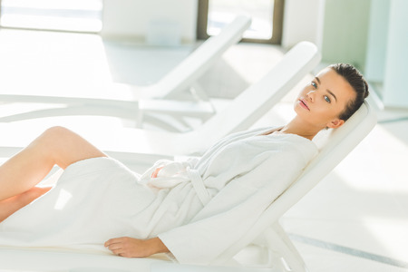 beautiful young woman in bathrobe lying on sunbed at spa