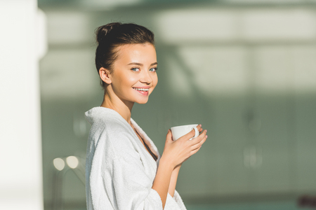 smiling young woman in bathrobe with cup of coffee at spa