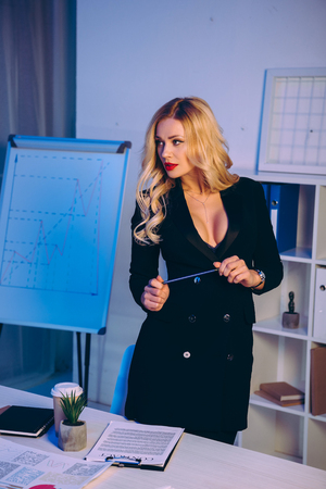 seductive businesswoman standing near diagram chart with pencil